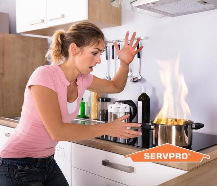 women at kitchen stove with fire