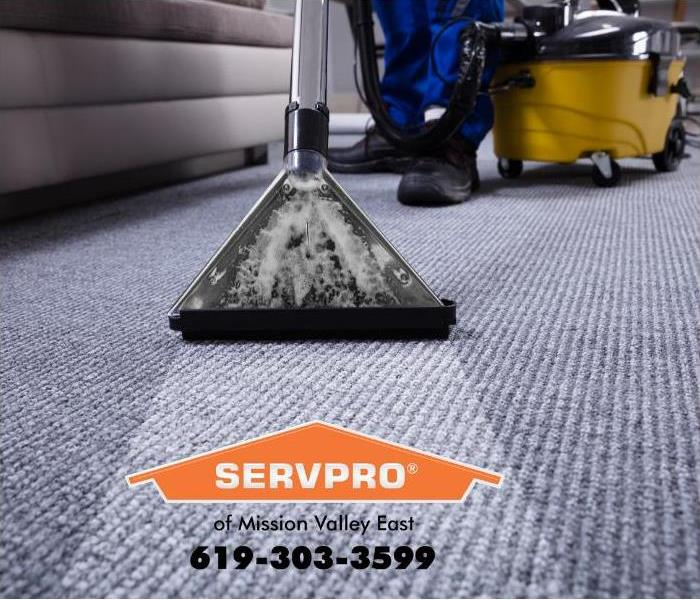 A commercial carpet cleaning wand is being used to deep clean a carpet in an office.
