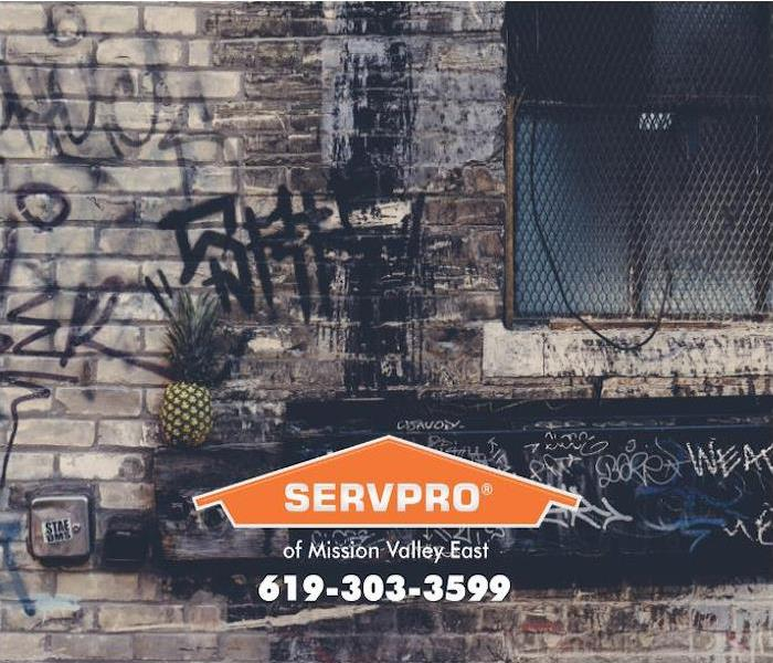 The exterior brick wall of a commercial building is shown covered in graffiti.
